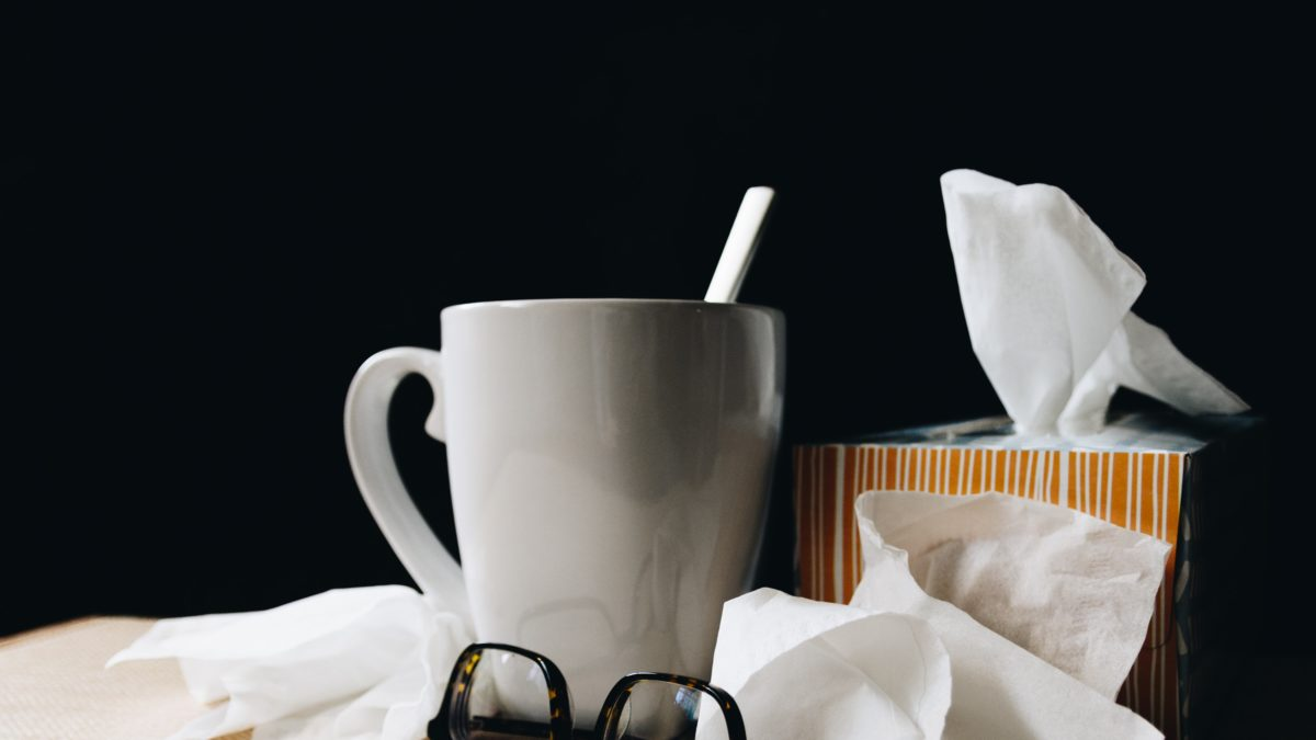 Mug, tissues, glasses on nightstand